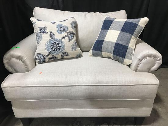 Beige Upholstered Love Seat With Pillow