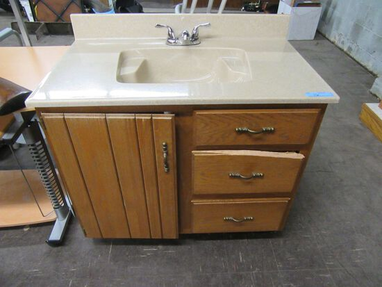 BATHROOM SINK WITH FIXTURE AND CABINET. DRAWER NEEDS REPAIRED.