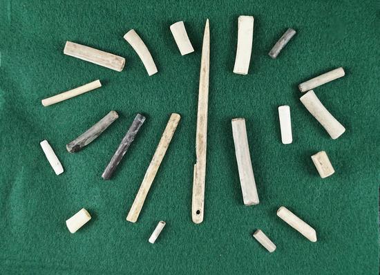 "Set including a 4 1/4"" long bone needle and 19 bone beads."