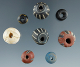 Group of 8 beads including a round opalescent, 4 large polycromes with stripes, 1 inlaid Roman, etc.
