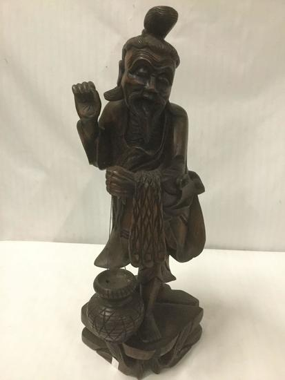 Carved wooden state of an Asian man carrying a jar and a net or pelts