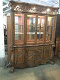 Massive antique style modern hutch cabinet with lighted display and ornate design
