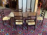Antique wooden dining table with 6 matching ladder-back wicker seat chairs - dark finish
