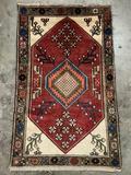 Vintage handmade wool rug with floral design, in red & neutrals - trimmed fringe on one side