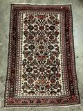 Vintage wool rug with intricate floral design in brown and red tones with orange/pink highlights