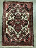 Vintage small wool rig, red tones with floral design - symmetrical ornate pattern