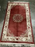 Thick wool rug with fringe, natural red tones with geometric and floral designs