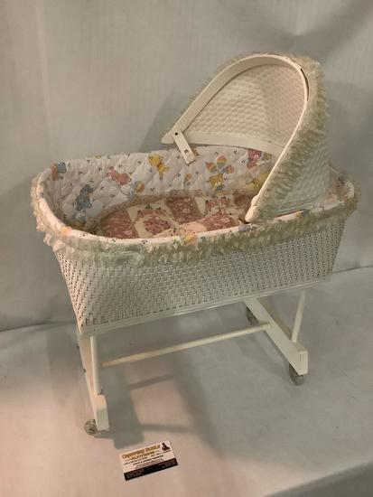 Vintage white painted wood and wicker baby doll bassinet on wheels, approx 18x14x24 inches.