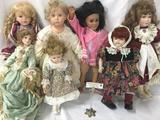 Seven porcelain and vinyl dolls from makers like My Twinn. Largest doll is approx. 24x12x4 inches.