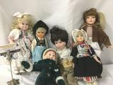 Six porcelain and vinyl dolls from Marian Yu Designs, Seymour Mann, and others. Largest doll is