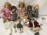 9x porcelain, composite and vinyl dolls. Largest doll measures approximately 16x6x4 inches.