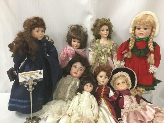 Eight porcelain and composite dolls from makers like Brinns. Largest doll measures approximately