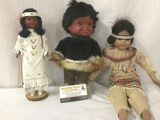 Three porcelain, wood, and vinyl dolls with indigenous garb, from makers like Regal. Largest doll