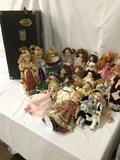 Twenty-three porcelain dolls in a vintage luggage trunk. From makers like Seymour Mann and Heritage