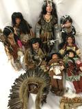 Eight porcelain dolls in indigenous garb from makers like Goldenvale, Cathay Collection, Traditions,