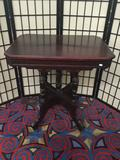 Antique Eastlake style parlor table with wooden caster and carved legs