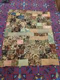 Vintage hand made quilt feat. various floral patterns, and checkered with many fabrics