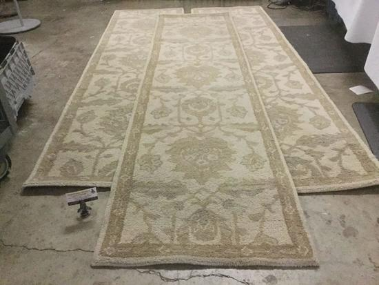 Three white Indian wool rugs with floral patterns from L.G.Sourcing Inc. approx. 96x25 inches each.