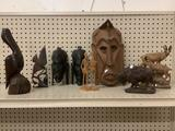 9x carved collectibles; ethnic masks, Don Quixote, pelican, buffalo composite, largest 12x8 inches