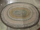 Oval shaped earth tone woven rug, approx 75x92 inches.