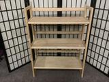 Three tiered wooden shelf, folds down for storage, approx. 28x12x39 inches.