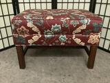 Small red cushioned wooden bench w/floral designs, approx. 28x20x19 inches.