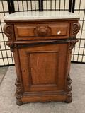 Antique wood carved nightstand with marble top, approx 20 x 16 x 31 inches. Needs repair. Sold as is