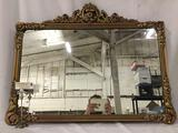 Vintage hand carved wall hanging mirror w/gold tone floral detailing. Approx. 36x2x28 inches.