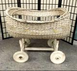 Vintage wicker and wood painted baby bassinet on wheels. Approx 36x34x32 inches.