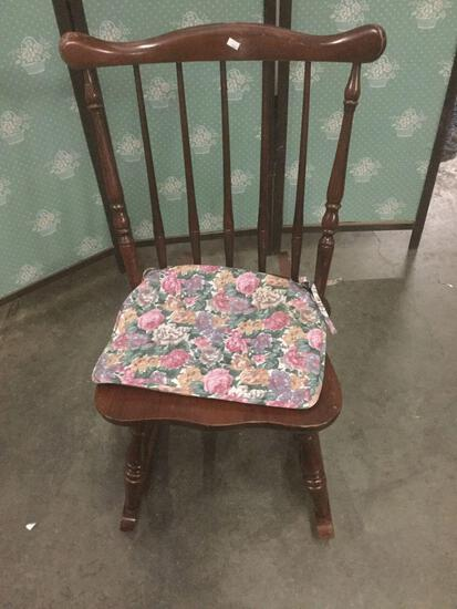 Vintage rocking chair with floral seat cushion.