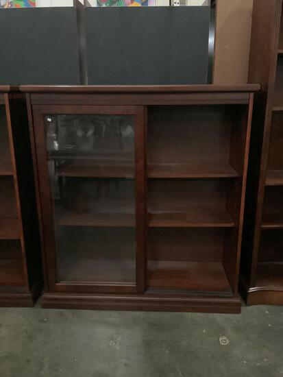 Modern glass front sliding-door display cabinet. Matches following lot. Approx 48x52x17 inches.