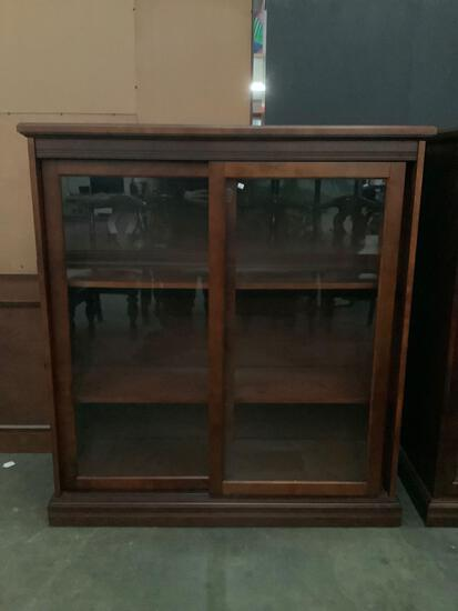 Modern glass front sliding-door display cabinet. Approx 48x52x17 inches. Matches previous lot.
