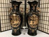 Pair of large ornate black vases w/ dragon handles, regal dining scene, fluted lip, & floral designs