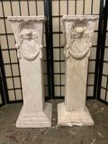 Pair of plaster pillars featuring a cherub theme. One has some damage. Approx 29x10x10 inches.