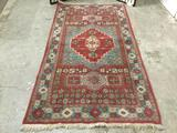 Vintage red & blue wool rug w/ floral designs & fringe. Approx. 94x49 inches.