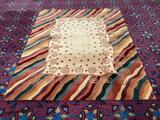 Handmade Momeni beige wool rug w/multi-color border & swirling designs. Approx. 115x91 inches.
