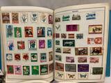 2 albums w/ hundreds of vintage international postage stamps. Largest book approx 12x9.5x2 in.