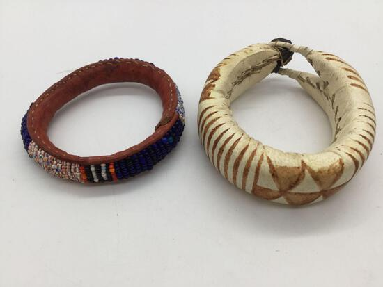 Pair of vintage leather African bracelets. One is beaded. Largest approx 3.5x3x1 inches.