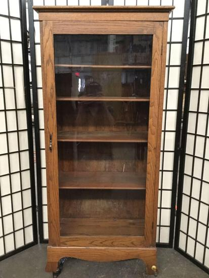 Wooden curio cabinet / book shelf on casters w/ some wear/missing wheel