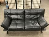 Black vinyl convertible two-seater couch, turns into bed, shows wear, approx. 70x36x30 inches