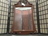 Wood frame wall mirror w/ regal detailing, approx 45 x 26 inches.