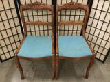 Pair of vintage wood carved chairs w/ floral designs on backrest & blue seats