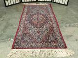 Classic Persian style wool area rug with classic blue/red design and fringe