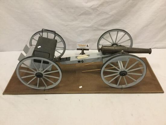 Large civil war-era cannon w/ ammunition trailer replica on wood stand.