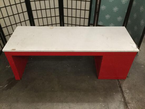 Red modern bench, has chip in top.