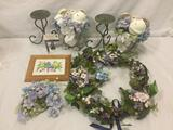Collection of home decor items, candle holders, stoneware donkeys with flowers, floral wreath, and