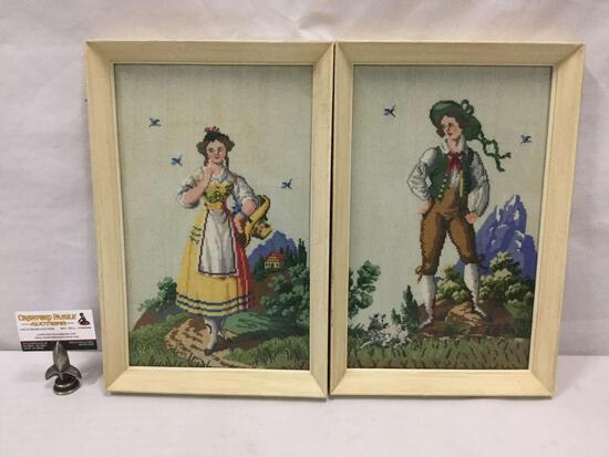 2 framed needlepoint art pieces of boy and girl in mountain scenes.