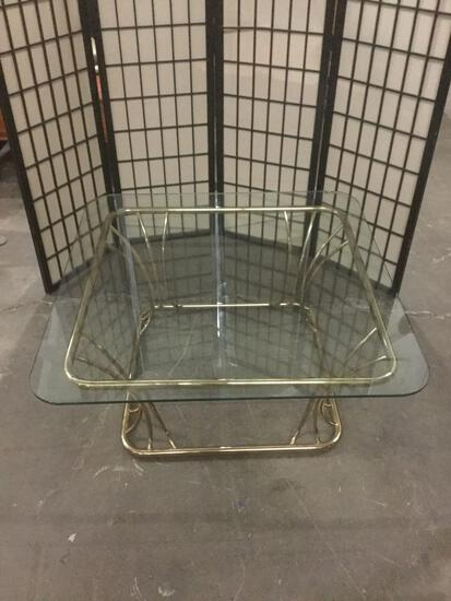 Gold tone frame glass top coffee table, glass has chip