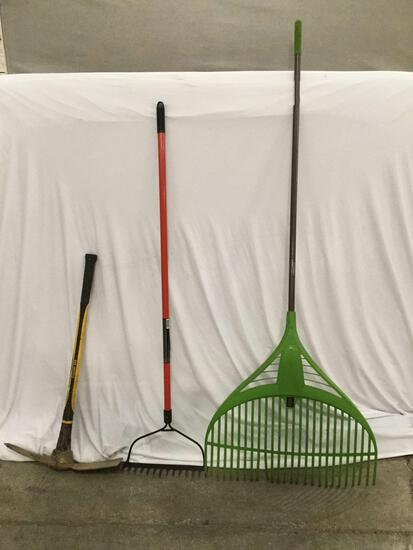 3 yard tools. Ames rake, Black and Decker fiberglass handle bow rake, and Collins Axe pick axe
