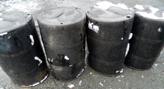 Four Black Hard Plastic Trash Barrels